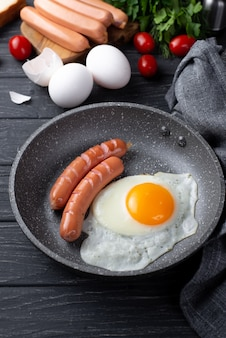 High angle of for breakfast egg and sausages in pan with tomatoes and herbs