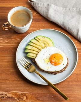 High angle of breakfast fried egg on plate with avocado and coffee