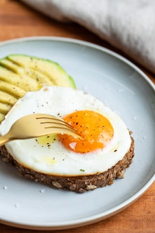 High angle of breakfast fried egg on plate with avocado and fork