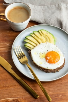 High angle of breakfast fried egg on plate with avocado