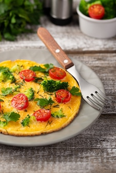High angle of breakfast omelette on plate with fork and herbs