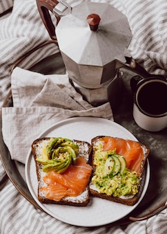 High angle of breakfast sandwiches with salmon and avocado in bed