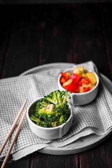 High angle of broccoli and bell pepper in cups on plate
