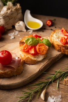 High angle bruschettas with prosciutto and tomatoes on cutting board