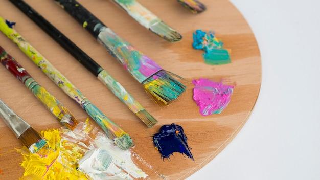 Alto angolo di pennelli con vernice e tavolozza