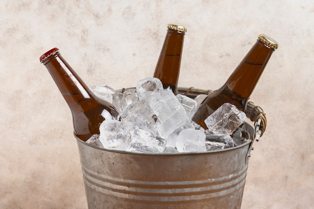 High angle bucket with ice cubes and beer bottles
