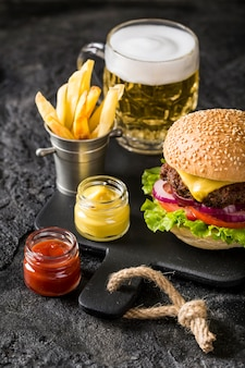 High angle burger on cutting board with fries, sauce and beer