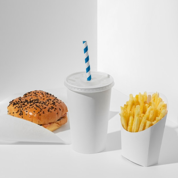 High angle burger and fries in packaging with cup