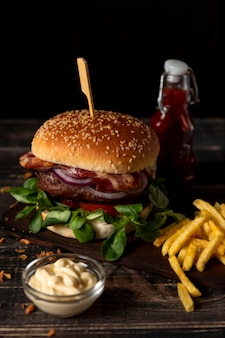 High angle burger and fries with sauces on table