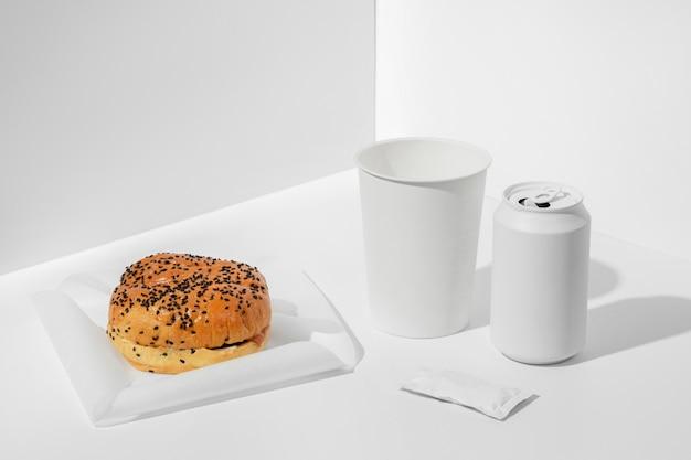 Бургер под высоким углом с пустой содовой и чашкой