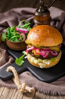 High angle burger with pickles on cutting board