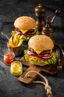 High angle burgers on cutting board with fries and sauces