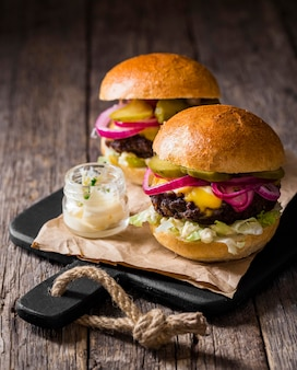 High angle burgers with pickles on cutting board