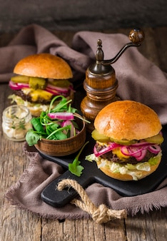High angle burgers with pickles and red onion on cutting board