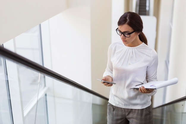 High angle of businesswoman on escalator with smartphone and notepad