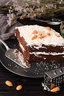 High angle of cake on plate with almonds and grater