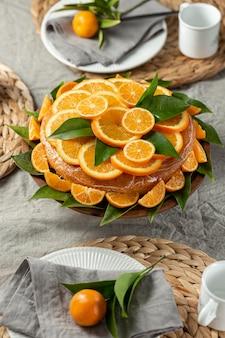 Alto angolo di torta con fette d'arancia e foglie