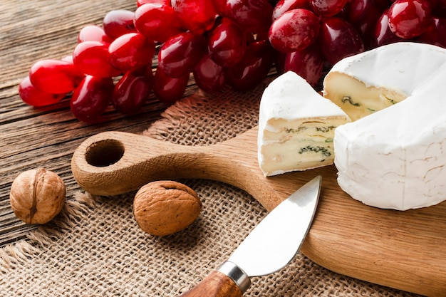 High angle camembert grapes and walnuts on wooden cutting board