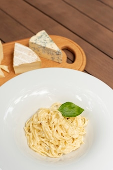 High angle of carbonara pasta on wooden table
