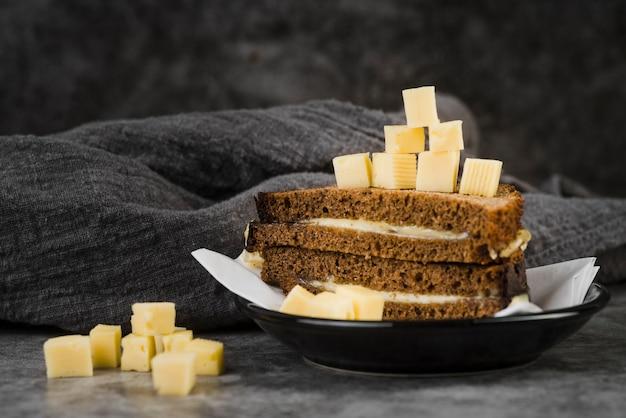 Высокий угол бутерброд с сыром на тарелке