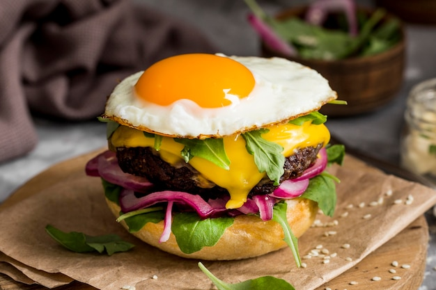 High angle cheeseburger with fried egg on cutting board