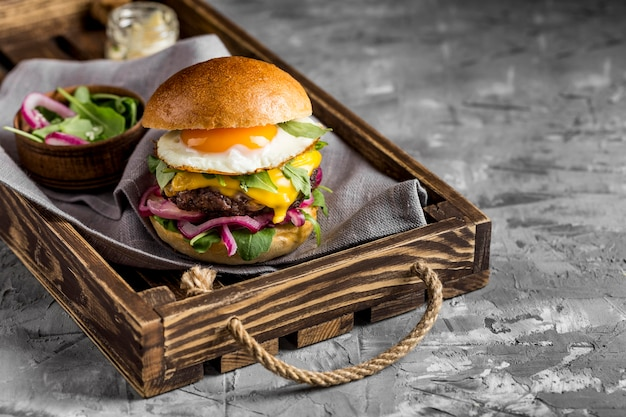 High angle cheeseburger with fried egg on tray