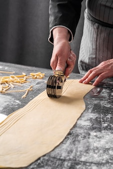 High angle of chef cutting dough strips