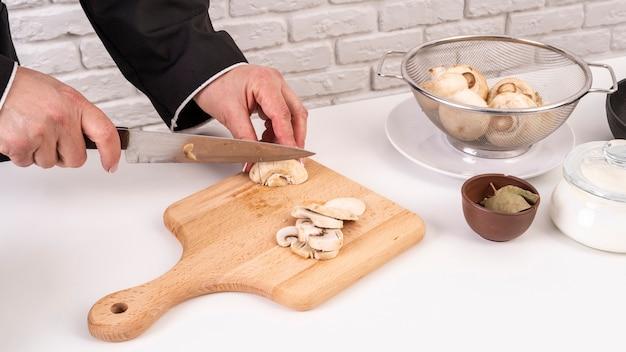 Alto angolo del cuoco unico che prepara e che taglia i funghi