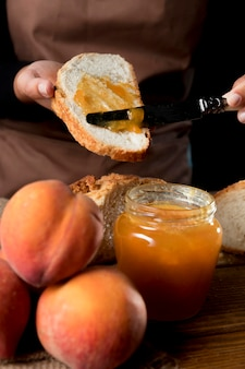 Angolo alto del cuoco unico che spande la gelatina di pesca su pane