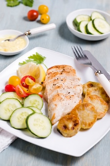 High angle of chicken breast with assortment of vegetables