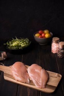 High angle chicken breast on wooden board with ingredients