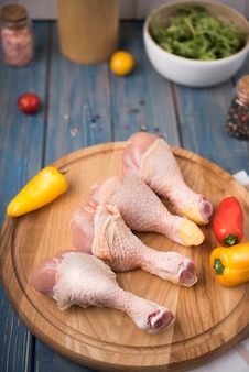 High angle chicken drumsticks on wooden board with peppers and tomatoes