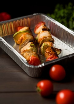 High angle chicken skewers on tray with cherry tomatoes