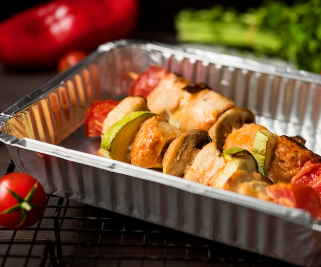 High angle chicken skewers on tray with red pepper and tomatoes