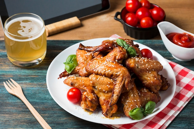 High angle chicken wings on plate with cherry tomatoes