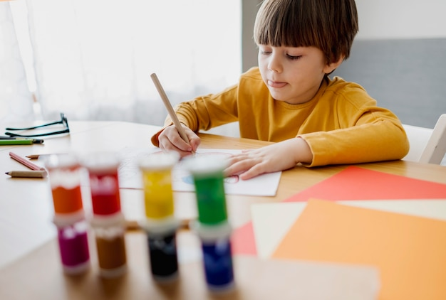 High angle of child drawing and learning at home