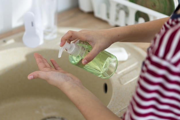 Alto angolo delle mani di lavaggio del bambino con sapone liquido