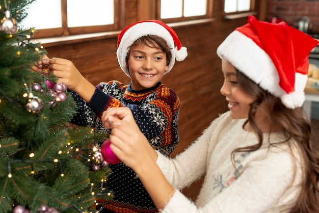 High angle children decorating the christmas tree