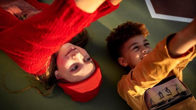バスケットボールのフィールドで一緒に横たわっている高角度の子供たち