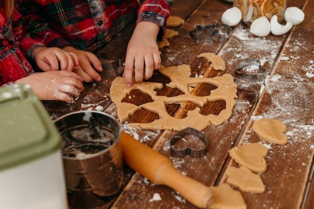 Дети под высоким углом делают печенье вместе дома