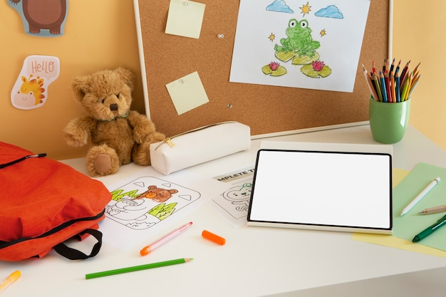 High angle of children's desk with book bag and tablet