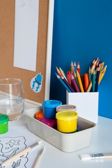 High angle of children's desk with paint and drawing