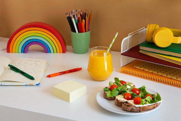 High angle of children's desk with sandwiches and orange juice
