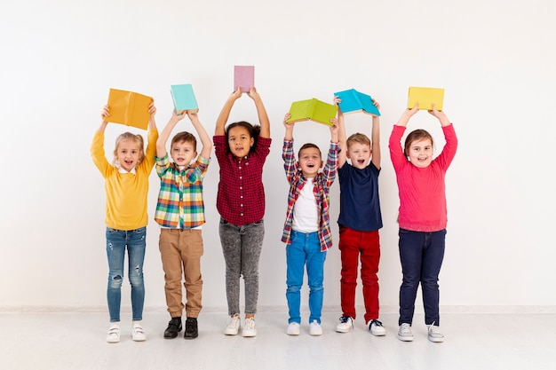 High angle childrens holding books above heads