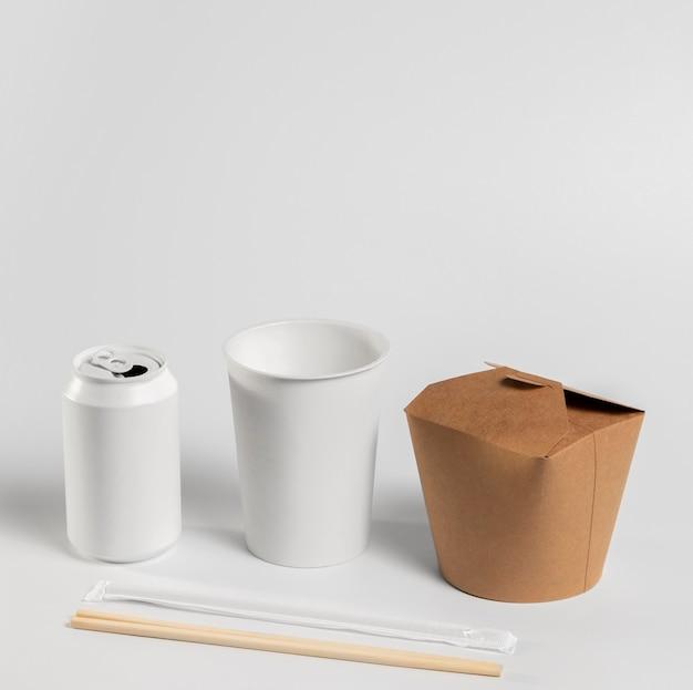 빈 음료수 캔과 컵이있는 높은 각도의 중국 음식 패키지