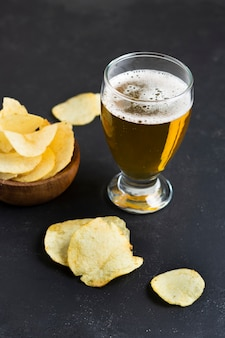 High angle chips beside glass with beer