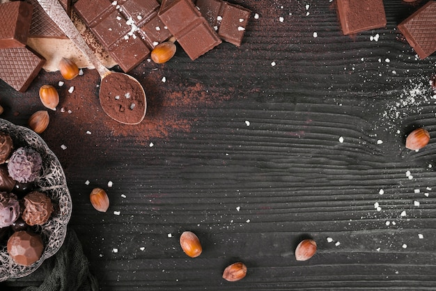 High angle chocolate bars and spoon with cocoa powder and copy space
