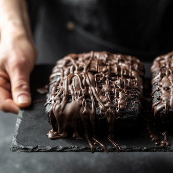 Alto angolo di torta al cioccolato tenuto dal pasticcere