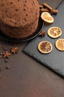 Alto angolo di torta al cioccolato con cacao in polvere e agrumi secchi