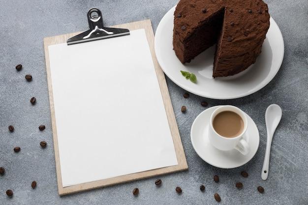 Alto angolo di torta al cioccolato con blocco note e caffè